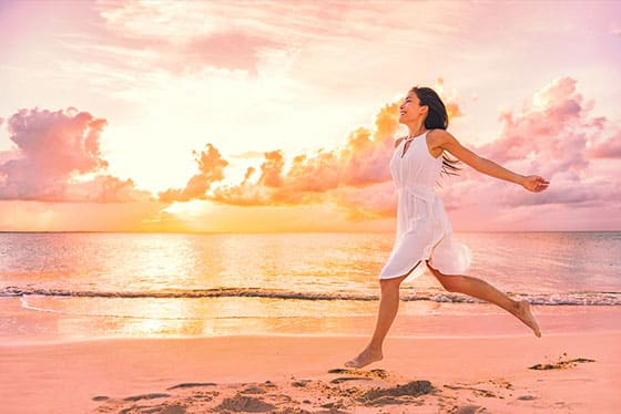 Peaceful woman along shore of beach demonstrating mindfulness in action