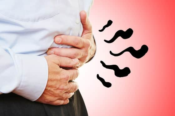 Man holding stomach with SIBO abdominal pain